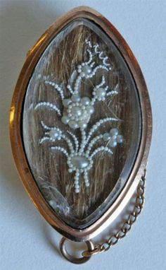 An antique mourning brooch with seed pearl floral design over hair under glass. Circa 1790