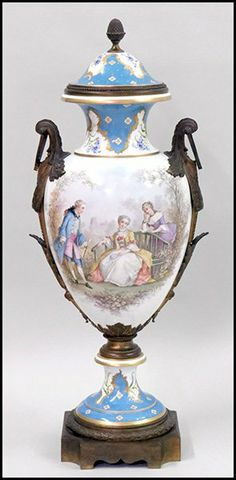 A 19TH CENTURY FRENCH SEVRES PAINTED AND BRONZE MOUNTED COVERED URN DEPICTING FIGURES IN COURT DRESS
