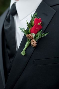 Groom wearing red rose, pine cone and pine boutonniere for a winter wedding