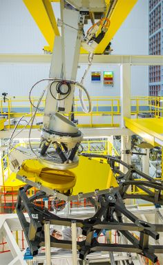 Webb Telescope Crew Flexes Robotic Arm at NASA  The robotic arm lifts and lowers a golden James Webb Space Telescope flight spare primary mirror segment onto a test piece of backplane at NASA's Goddard Space Flight Center in Greenbelt, Md.
