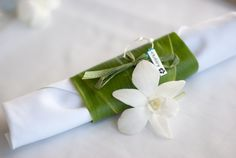 Ti Leaves are wrapped around the napkin for an organic, tropical feel.  DIY wine charms act as name tags for guest seating and a small white orchid adds the final touch.  Photo by Greg Hoxsie Photography.