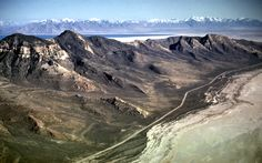 124-31: Stansbury Island on southwest side of Great Salt Lake, UT.  A beach of Lake Bonneville follows a contour on these dipping Paleozoic sediments. Looking SE - Wasatch Mtn Front in background (13Apr66)