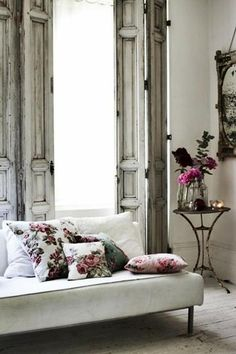 Source-My French Country Home Living Room The amazing  beautiful time worn bi-fold shutters certainly are the feature in this french living room.With equally worn pale floorboards  a delicately rust peeling side table, only adds to the romance.A simple settee scattered with a vintage rose print cushions, wild flowers casually placed in a vase  an antique time worn mirror