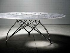 Joris Laarman's Leaf Table takes after his previous designs, which meld organic forms and intricate, modern designs. His pieces don't attempt to imitate organic forms, but obviously take their inspiration from them. The Leaf Table has a large tabletop with abstract leaf designs imposed on it. The legs of the table appear delicate while adding overall strength to the design.