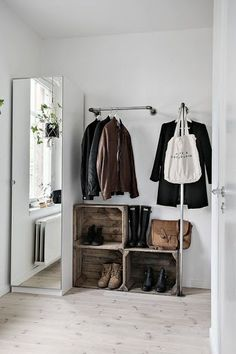 Rustic wooden fruit crates used as shoe storage boxes contrast well with the Scandinavian style white walls and whitewashed floors in this entryway.