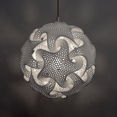 """This light scuplture expresses the unity between the four elements of the natural world and the spiritual wholeness of the universe - what the artist Bathsheba Grossman likes to refer to as the quintrino.  This lamp is based on the dodecahedron, the most mystical of the platonic solids: """"Mathematically, this object adds complexity to the original dodecahedron by bringing in a rotation, so that the object becomes different from its mirror reflection...it's a symmetry that is rarely seen; ..."""