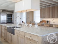 Coastal kitchen with natural cabinets and white exposed trusses.