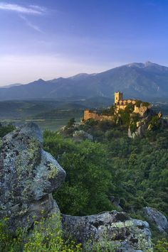 The village of Eus perched on a hilltop with the Pic de Canigou beyond, the Pyrenees, Languedoc-Rousillon, France