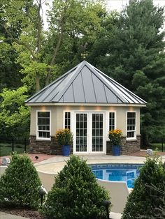 Pool house with metal roof and copper weather vane.