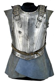 "Breast-plate ribbed at the centre, with blow on the right, a row of brass rivets at the margins, the border slightly bent toward the outside. Engraved with linear bands, at the top the crowned stamp ""N"". Back-plate with blow, decorated with bands and rivets; provided with straps cuirassed with iron plaques. Assembled on a mannequin with wooden pedestal.provenance: Europedimensions: height 46 cm.  dating: mid-17th Century"