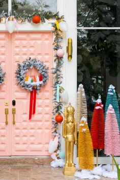 photo of a front entrance decorated for christmas with a pink door