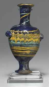 A CORE-FORMED GLASS UNGUENTARIUM EASTERN MEDITERRANEAN, CIRCA 3RD CENTURY B.C. Cobalt blue in color, the ovoid body with rounded shoulders, a flaring long cylindrical neck, a disk rim, and high cylindrical foot splaying to the flat base, with opaque turquoise and yellow marvered threads wound spirally along the rim, neck and body and tooled into a zigzag pattern on the body, shallow vertical grooves from the tooling, with applied twin blue lugs on the body 4 5/8 in. (11.7 cm.) high