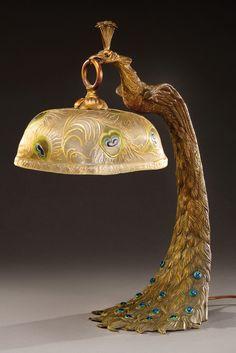 A.ROLLET (XIX-XXème) Importante lampe en bronze à patine médaille figurant un paon tenant dans son bec un abat-jour en verre attribué à Montjoye à décor de plumage de paon dans les tons verts, bleus et dorés sur fond givré opaque. La base est agrémentée de cabochons polychromes imitant la queue. Signée «A.Rollet». Vers 1920. H : 51,5 cm A large bronze lamp representing a peacock holding a glass shade decorated with peacock feathers and attributed to Montjoye. Signed «A.Rollet». Circa 1920. H…