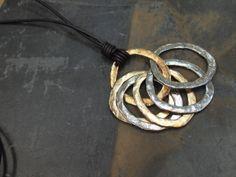 Collar de aros de zamak plata y dorados y cordón de cuero.