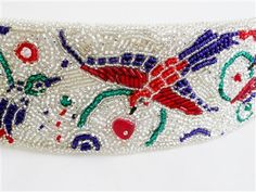 "Crystal Birds Cuff -  This unique cuff displays colorful birds made from ruby, sapphire, and emerald Czech and Japanese Seed Beads, embroidered between silver-lined Seed Beads. Finished with a textured, white leather backing, and a silver-toned multi-strand slide lock tube clasp. Bracelet measures 8"" long and 2 ¼"" wide."