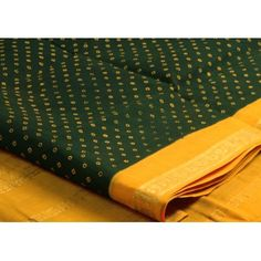 The classic Sungudi small dots in a dark green body and a lemon yellow pallu adding the required zest!
