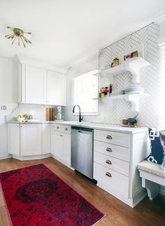 White kitchen with modern chandelier, raspberry rug, chrome appliances and bright natural light
