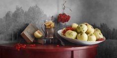 Plate of Autumn Apples https://500px.com/photo/176682429/plate-of-autumn-apples-by-nikolay-panov?utm_medium=pinterest&utm_campaign=nativeshare&utm_content=web&utm_source=500px Fruit still life photography with white plate of autumn yellow green apples, old books, cup of tea and bright red berries on painted tabletop with rustic landscape on background #NikolayPanov