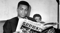 Muhammad Ali, back then Cassius Clay, reads the Daily News story about his victory over Zora Folley at the Midtown Motor Inn in New York City.