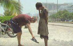 a man gives his sandals to a homeless girl in Rio de janeiro