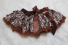 Chocolate Cheetah Pettiskirt - although for a baby - use of fabric gathered and feathers attached to hem.  Cute idea