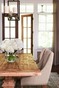Love the simple flower arrangement on this dining room table. French doors bring light into the room.