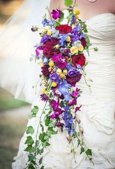 Super Fun Jewel Tone Cascading Bouquet Showcasing: Sangria Dahlias, Deep Red Cabbage Roses, Purple Chrysanthemums, Fuchsia Orchids, Blue Delphinium, Purple Lisianthus, Yellow Craspedia, Yellow Roses, Red & Pink Hypericum Berries, & Beautiful Trailing Ivy^^^^