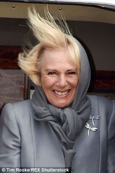 Easy breezy! Camilla still managed a smile as she left the plane in the windy conditions