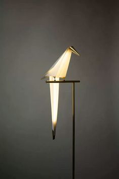 """"""" Perch Light is a playful, paper light design that looks like a small, abstract bird sitting quietly on the edge of a ledge. Created by London-based Umut Yamac, the interactive light comes alive and..."""