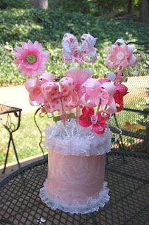 bow bouquet!  Clever shower gift! The bottom could easily be some diapers with a blanket wrapped around and some ruffle headbands for decor.