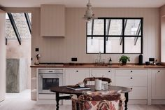 In four charming loft apartmentsdesigned byThe Renegade Real Estate Developers: Chan + Eayrs in London, paneled walls, painted in Farrow & Ball's palepink Setting Plaster, contrast with black steel-frame windows and beams.
