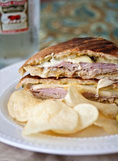 Cuban Paninis 4 ciabatta rolls or sub rolls 2 tablespoons spicy brown mustard 1/4 pound baked ham, thinly sliced 1/4 pound roast pork, thinly sliced 1/4 pound Swiss cheese, thinly sliced 10 thin dill pickle slices, approximately 2 whole pickles 1 tablespoon unsalted butter, room temperature