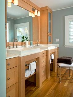 """""""These clients had quite a list of specific needs for their master bathroom,"""" says designer Kurt Hakansson. To create separate storage for each person, Kurt added two top wall cabinets on each side of the double vanity with adjustable shelves and convenient outlets. In the center, base cabinet drawers offer storage for common items. Towel bars placed under each sink provide easy access with a shelf below for extra towels."""
