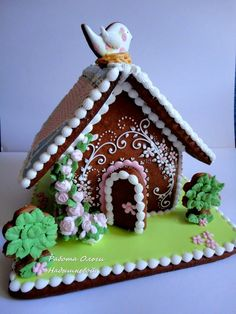 Springtime gingerbread house with flowers, nesting bird, grass, bushes