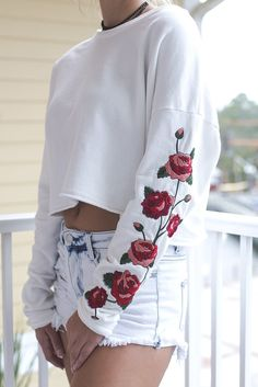 White crop top features rose applique on the sleeves, long sleeves, and no lining Material is cotton Model Ali is 5'9 wearing a small Shop the look Bust Length