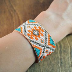 see what's up in shop today. Beadweaving on a loom was my first introduction to making jewelry. I could spend hours designing patterns and string beads. So upon finding my old loom I decided to try some new designs. This bracelet features a star pattern I designed inspired by woven kilim rug patterns I love so much. For this cuff I used orange turquoise grey and white seed beads woven between greek leather cords for stability with a bright peach silk thread. At each end is a deer hide…