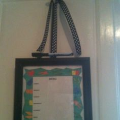Dry Erase Menu Board from a picture frame with glass. Print a sheet from your computer, put it in frame. Add magnet at top to hold a magnetized dry erase market. Add ribbon tie and hang from top of cabinet door with hook or hang on wall.