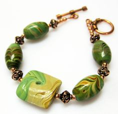 Sale 35% off regular price $42.00. Wonderful green and tan swirl lampwork beads combined with copper equal one beautiful lampwork bracelet.