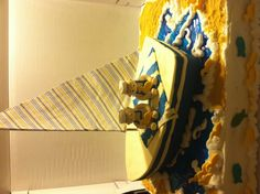 Sailor & sailboat baby shower cake.  Yellow cake covered in butter cream.  The boat is made of rice Krispy treats covered in fondant.  The sail is made of clothe.  The water is isomalt.  The babies, ducks & fish are made of fondant.