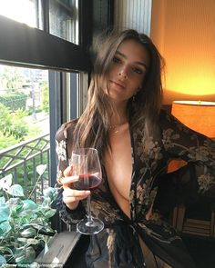 Braless: Emily Ratajkowski showed off her ample cleavage and a flash of her underwear in a semi-sheer kimono as she sipped on a glass of red wine on Instagram on Thursday