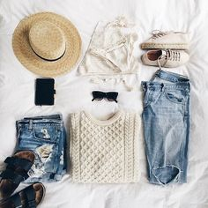 Distressed denim shorts, a cable knit sweater, a straw hat, lingerie, and sneakers.