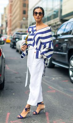 Street style look com camisa listrada e calça branca.