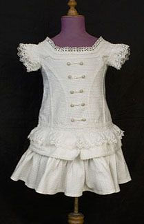 Child's fancy cotton dress, c.1880. Antique children's clothing has an enduring charm. This fine piece made from crisp white cotton piqué is a delightful example. The texture of the weave is accentuated with bands of braided cotton trim and eyelet ruffles. The rows of fabric-covered buttons are decorative in front and functional in back. The dress is absolutely perfect, although four buttons in back are old replacements.