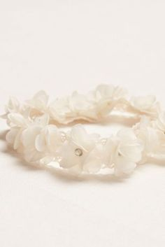 A fun headband that can take hairstylesfrom your special day to night.  Stretch headband with soft flowers each adorned with crystal centers.  Available in Ivory.  Imported.