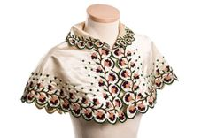 This wonderful cream silk capelet has scalloped edges embroidered with a delicate garland of chenille flowers. A shoulder cape like this would have been worn in the early 19th century with a fashionable Empire dress - a slender silhouette with high waist and puffed sleeves. It is likely that this one was worn by Elizabeth Cruger Guerin (1787-1874) who married John Cart, Jr. in Charleston in 1816.