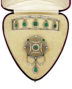 AN EDWARDIAN EMERALD AND DIAMOND SUITE. Comprising a choker necklace and a circular brooch / pendant of similar design, circa 1905, 16.2cm and 11.6cm long respectively, the brooch with detachable fitting and folding pendant loop, original fitted case by Garrard & Co. Ltd.