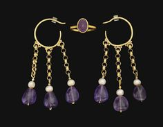 A PAIR OF BYZANTINE GOLD, AMETHYST AND PEARL EARRINGS   CIRCA 5TH-6TH CENTURY A.D.   Each composed of a plain open hoop, with three loops along the length, each framed by granules, suspending lengths of double-linked loop chain, terminating in a pearl and an amethyst; together with a modern gold and amethyst finger ring