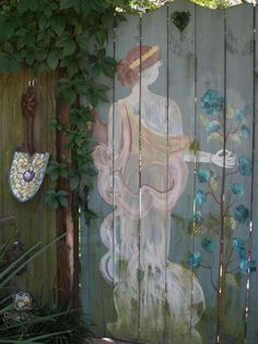 "My Back Yard Gate, I painted ""The Goddess Flora"" on it, and she shows the way. Notice my shovel head that I did mosaic on! I have had her on my gate for at least 6 years."