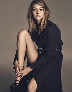 Flaunting some leg, Gigi Hadid models black trench coat for Vogue Magazine Japan December 2016