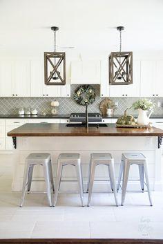 White kitchen cabinets wood chandeliers metal bar stools and quatrefoil gray backsplash